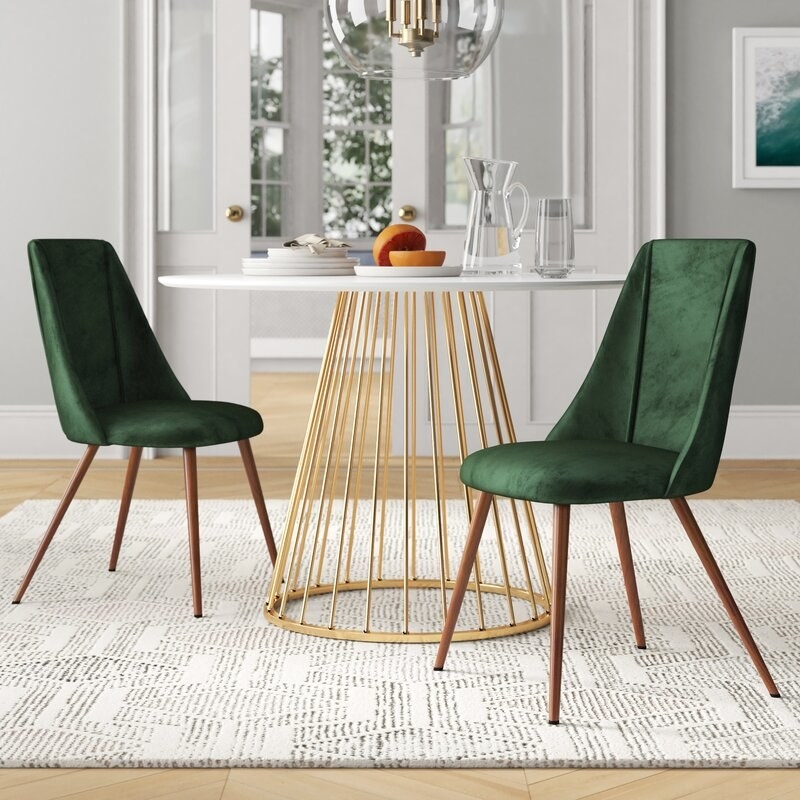 Two dark green upholstered small chairs