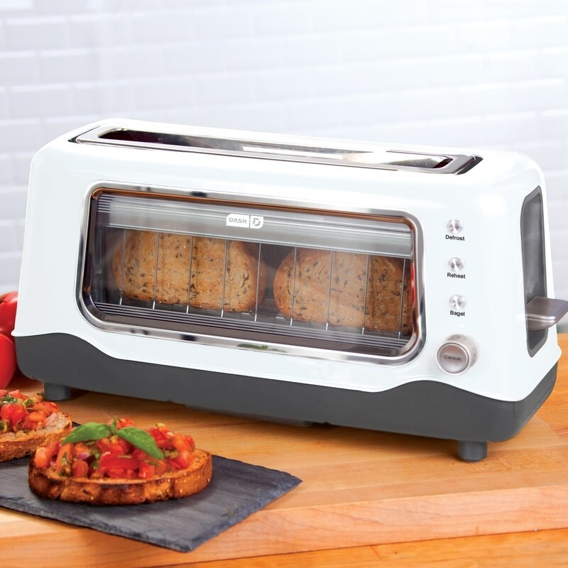 the white toaster with a window in front showing the toasting bread