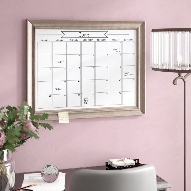 Dry erase calendar with a frame that is hung up on the wall