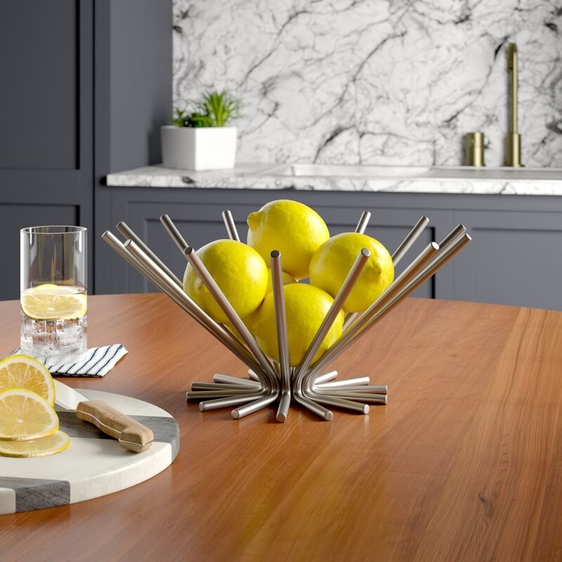 a silver fruit bowl that looks like an array of straws jutting out to form a basket