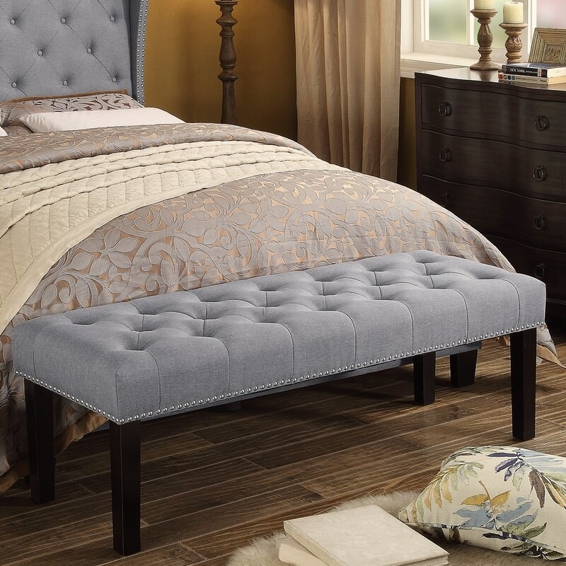 Gray upholstered bench at the end of a bed