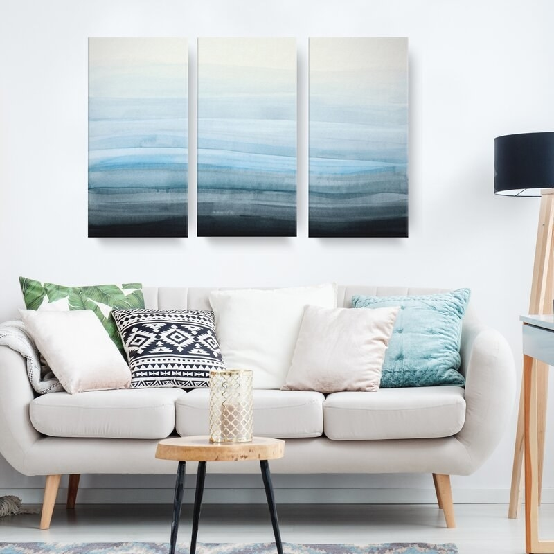 A painting sectioned into three canvases hanging in a living room