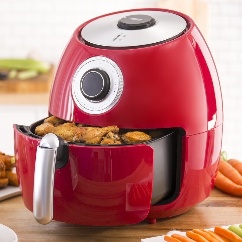 a red air fryer with chicken in the open drawer