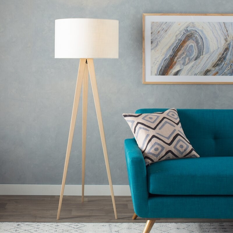 The tripod floor lamp with light brown legs and a white lamp shade