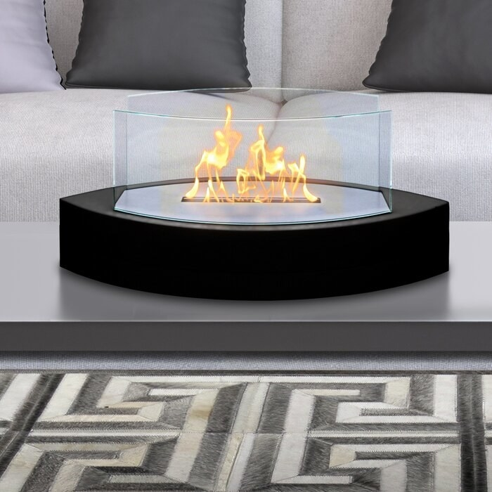 A propane tabletop fireplace with a black base in a living room.