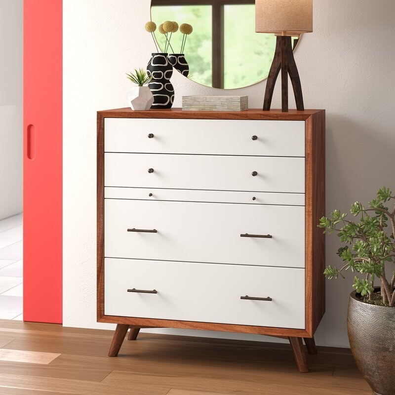 Dresser with a brown frame and legs and white drawer on the front in different sizes.