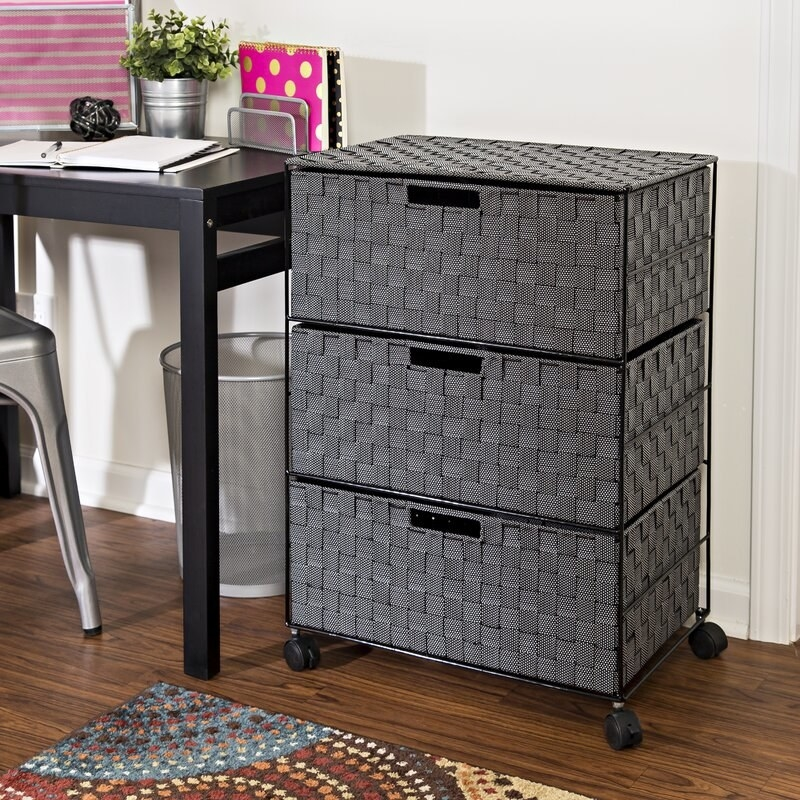 A wheeled storage chest with gray woven pull out shelves