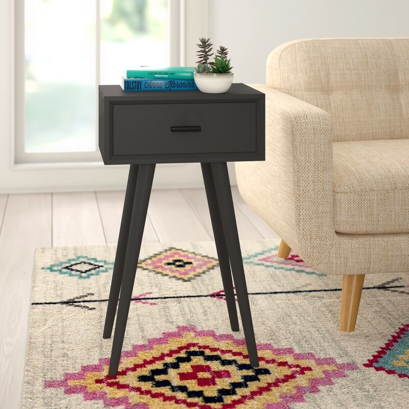 Black end table with a drawer and diagonal legs in a living room.