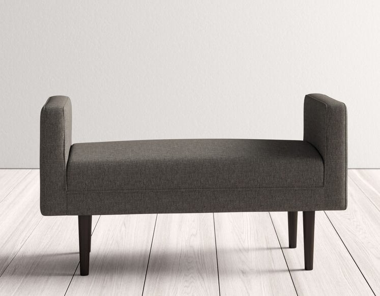The upholstered bench in grey with dark brown legs and taller arms on each side