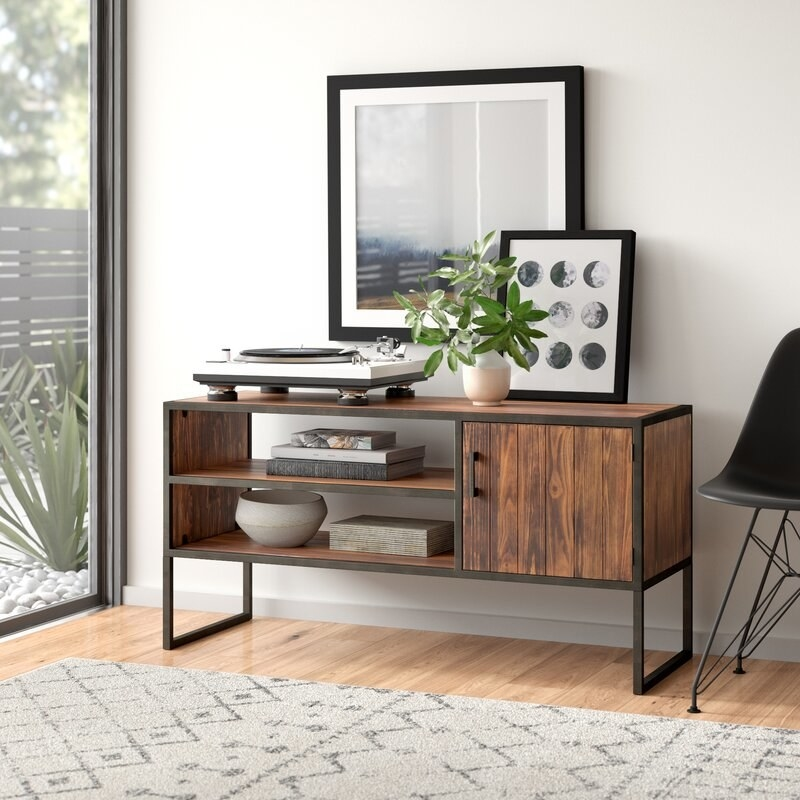 Long wood TV stand with dark metal legs, two shelves on the left side and a cabinet with a door on the right