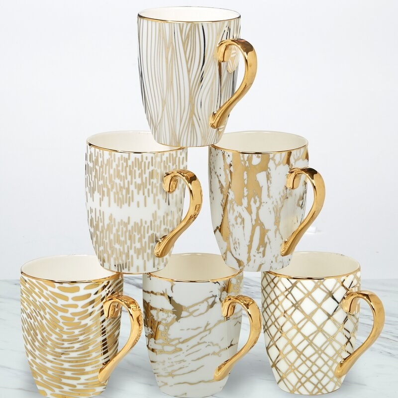 white mugs with different gold detailing on each