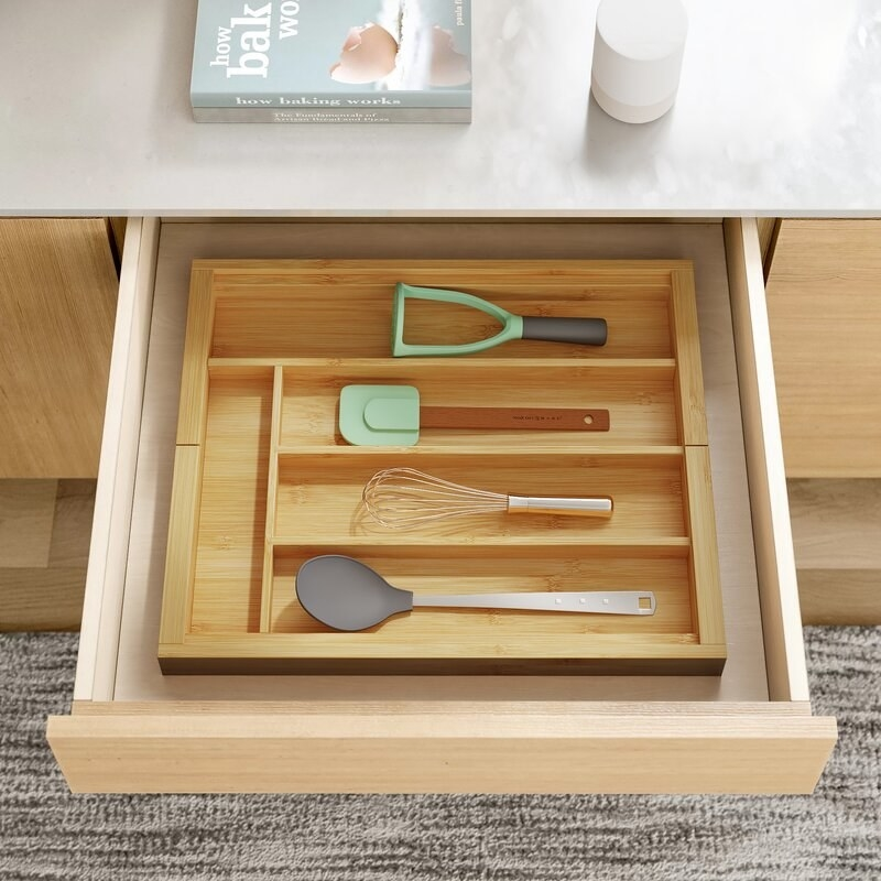 The organizer expanded in a drawer to fit perfectly and organize kitchen utensils