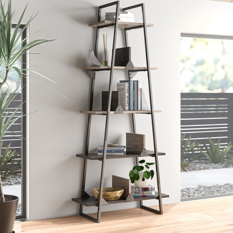Five-shelf bookcase where the shelves get smaller as they get higher with wood shelves and metal frame with books, plants, and trinkets on it