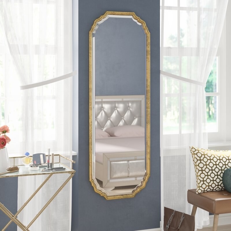 Wall mirror with gold trim hung in bedroom