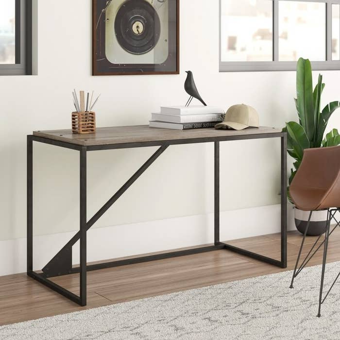 Brown wood-top desk with dark brown metal base with a piece going diagonally across the middle back