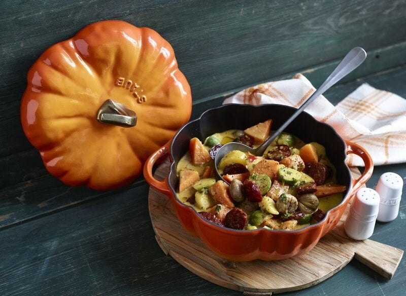 an orange pumpkin-shaped dutch oven with the lid off