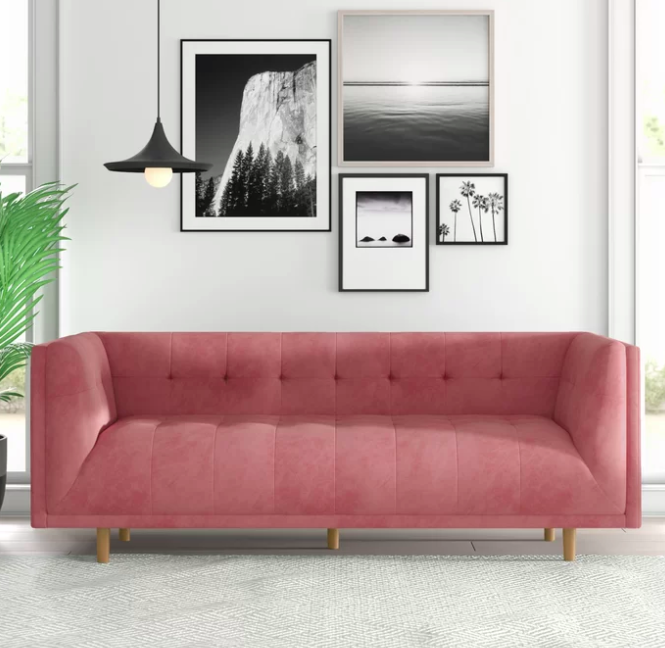 Blush velvet sofa against a white wall filled with black and white prints