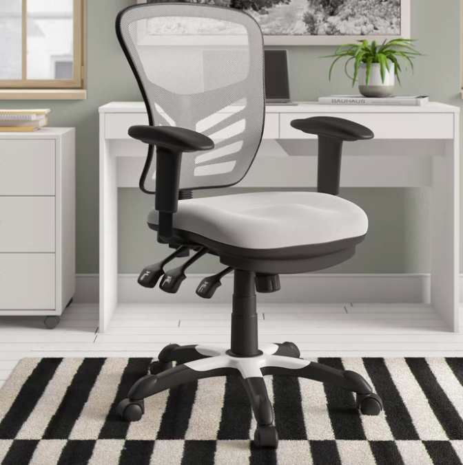Ergonomic black and light gray desk chair next to a white desk with drawers