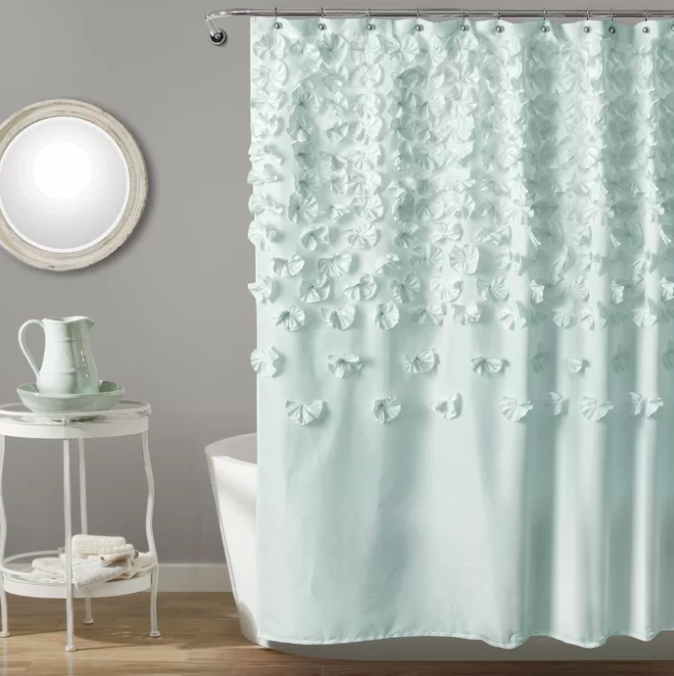 Light blue shower curtain with flower petal designs in front of a white tub on a hardwood floor