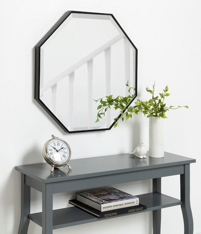 The octagon-shaped mirror with a black border above a console