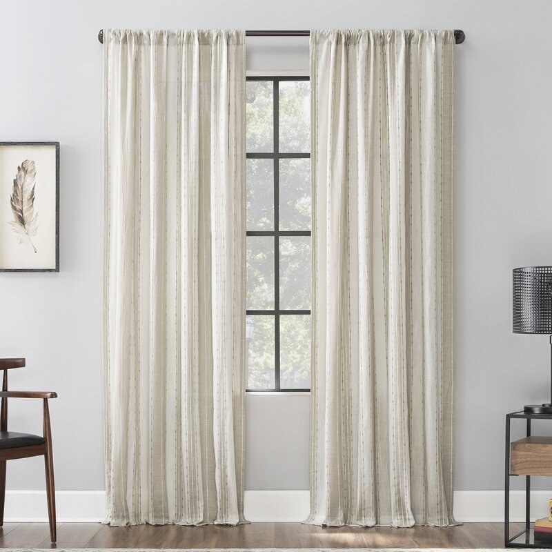 White curtains with a grey vertical stripe pattern on a window.