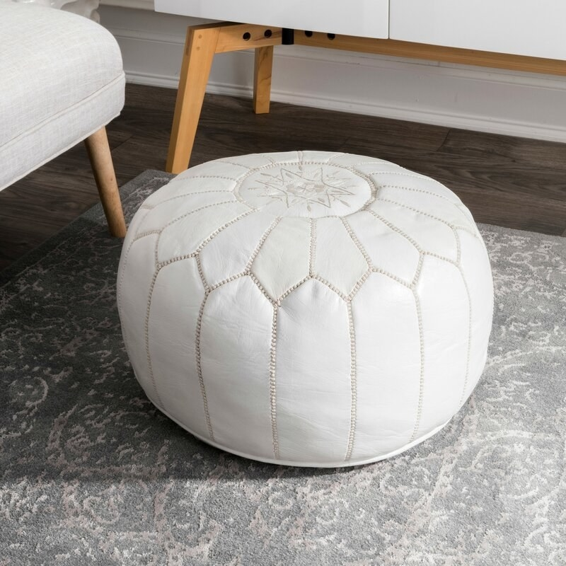The white leather circular pouf with an embroidered flower-like pattern on it