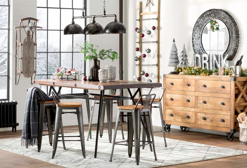 Four-piece wooden bar stool set around an elevated brown table in a dining room decorated with black industrial lights, sleds, and Christmas decor