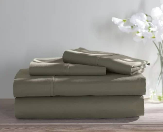 Sage green sheet set folded on a wooden shelf next to a vase with flowers