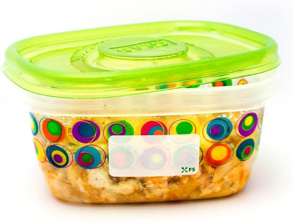 Food storage container with food in it and a label adhered to the outside of it