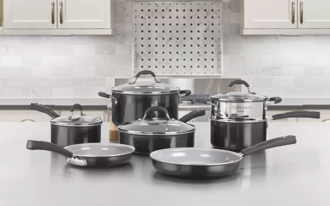 Eleven-piece Cuisinart black non-stick cooking set with pots and pans on a silver countertop