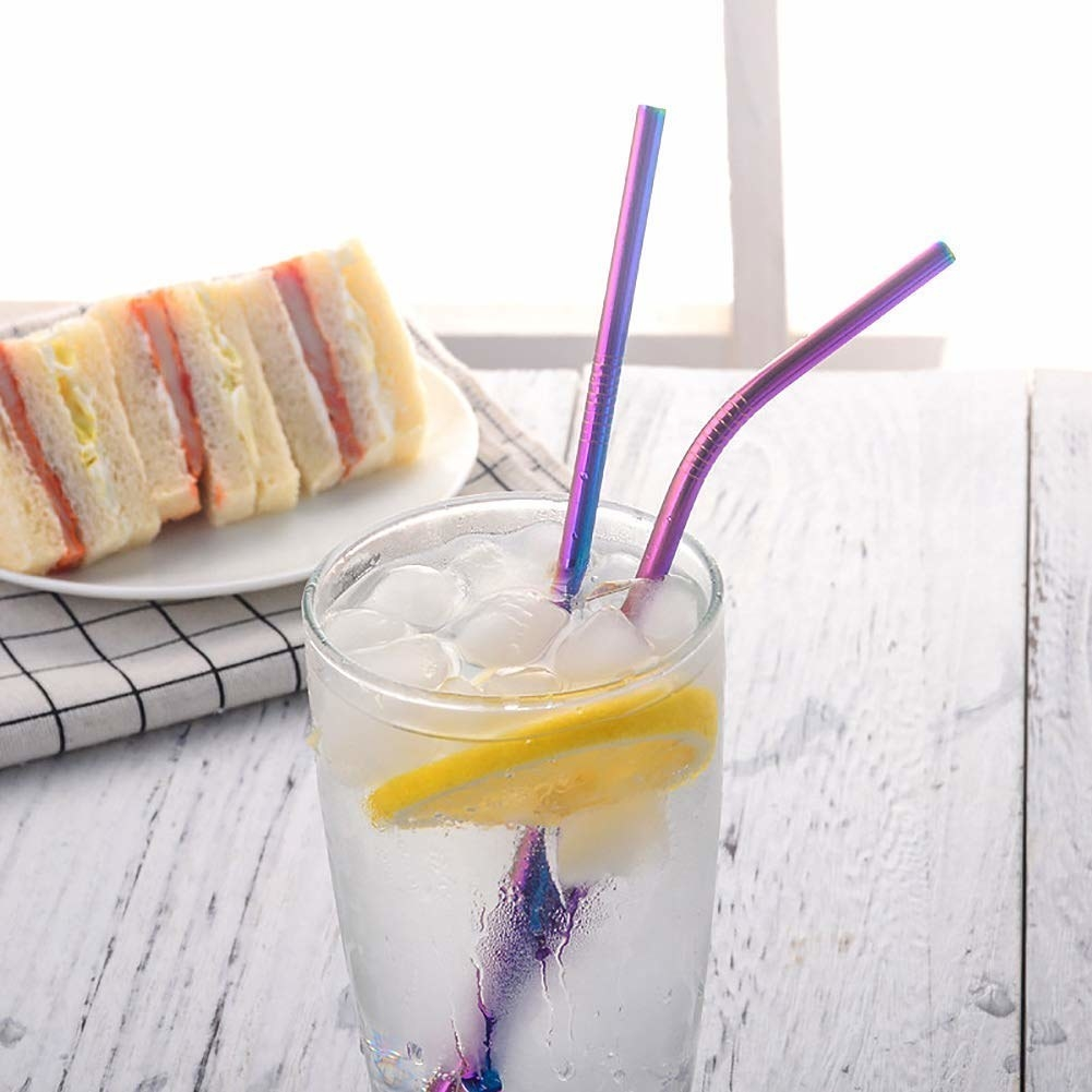 Two ombre metal straws kept in a glass of iced lemonade and a plate of sandwiches placed next to the glass.