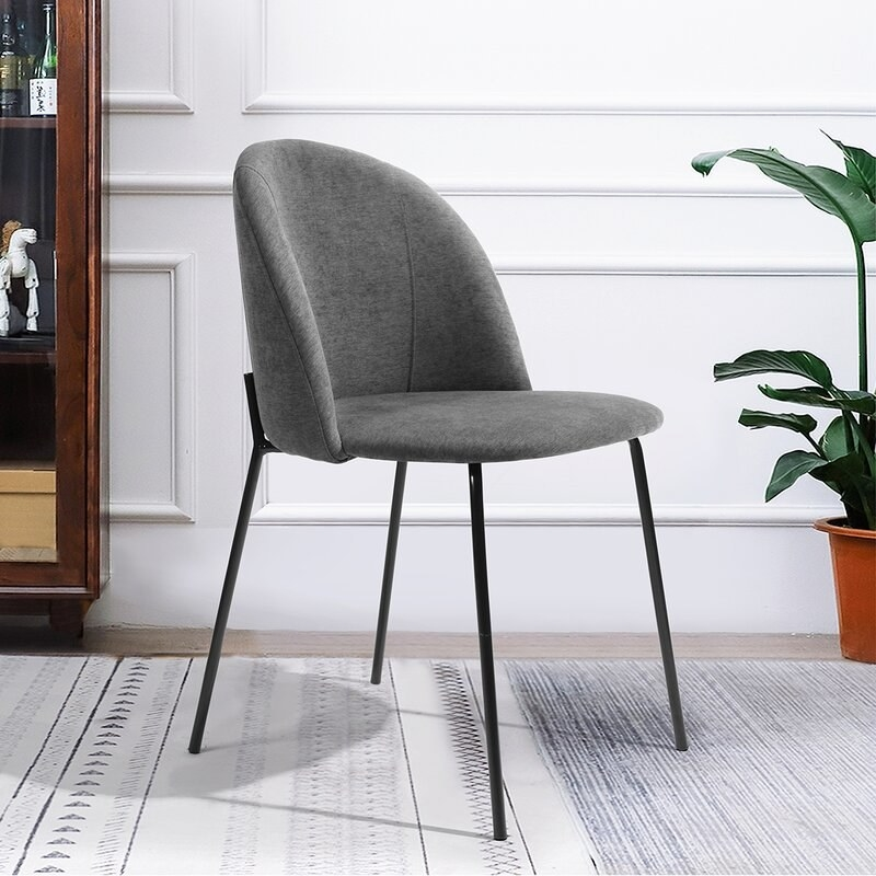 The grey upholstered chair with black legs.