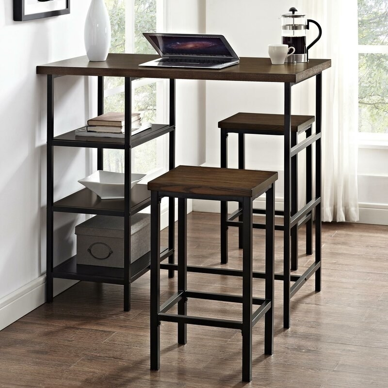 Brown wood-top table with black metal legs and three shelves on one side with two matching stools on either side of it.