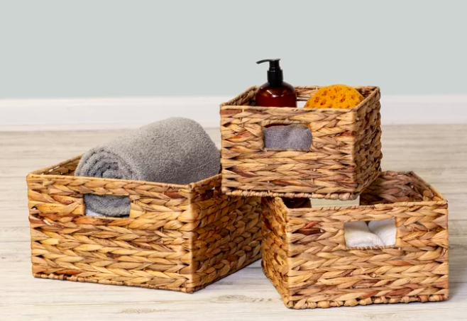 Three light brown wicker baskets filled with a gray towel, a dark brown container of soap, and more shower goods
