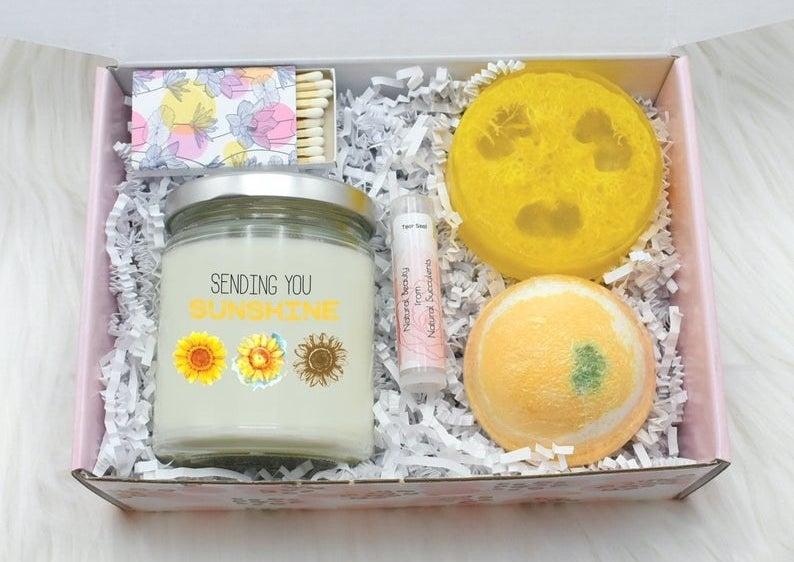The open box containing the candle, bath bomb, loofah soap, lip balm, and matches