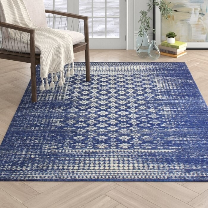 The Clarence Dark Blue Rug in a decorated sitting area