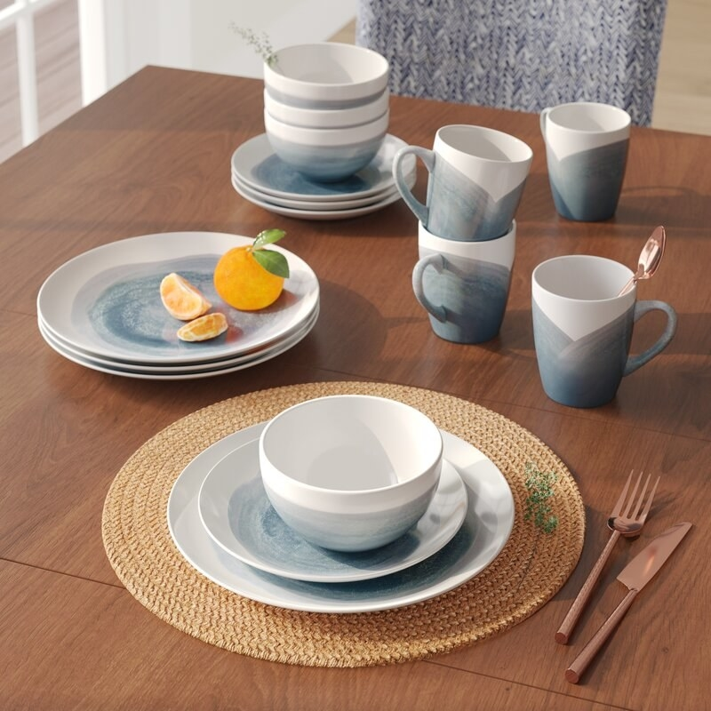 an array of mugs and dishes that are white with greyish-blue watercolored designs on them