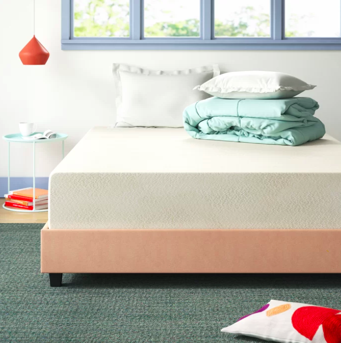 White memory foam mattress on pink bed next to little blue accent nightstand