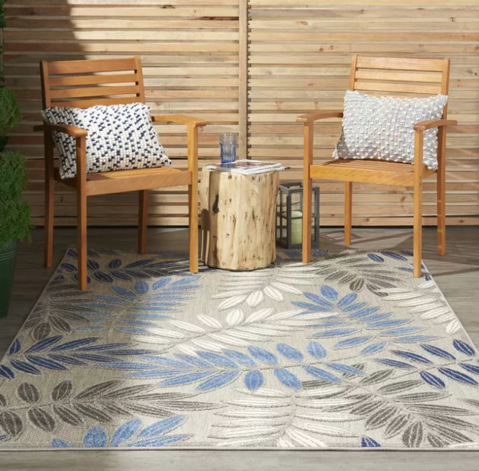 Gray, blue, and white leaf-printed outdoor rug next to two wooden patio chairs and a tree bark table