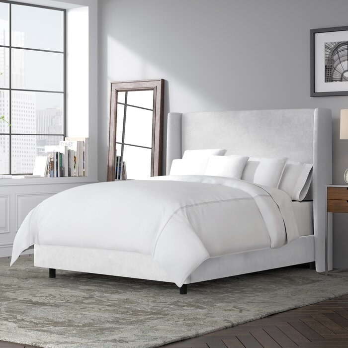 The White Goodrich Velvet Upholstered Standard Bed in a decorated bedroom