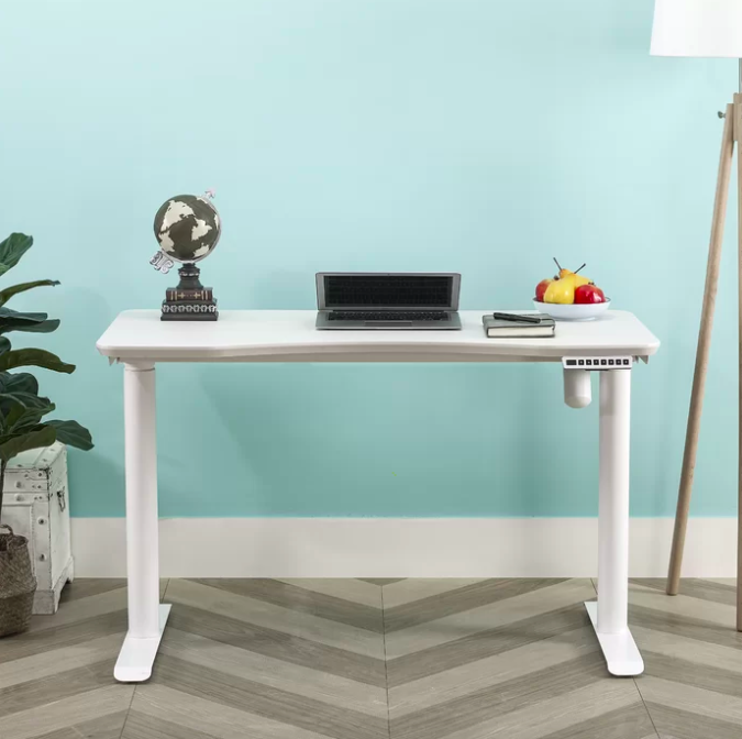 White height adjustable desk with a black laptop, globe statue, and bowl of fruit on top