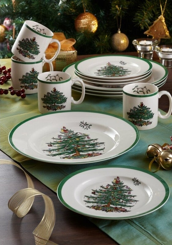 a set of plates and mugs with a christmas tree design on them and green edges