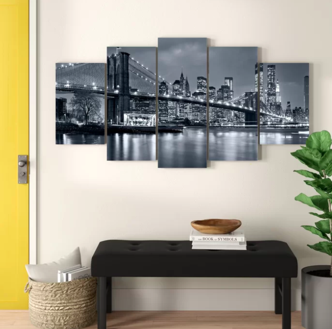 Five-piece canvas print with NYC city scene above a black entryway bench, wicker storage basket, and leafy green plant