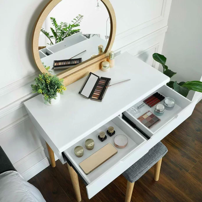 White makeup vanity with wooden circular mirror and two shelves filled with candles and makeup palettes
