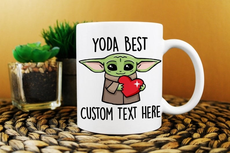 """The white mug with a picture of Baby Yoda holding a heart with the text at the top saying """"Yoda Best"""" and a spot for custom text available at the bottom"""