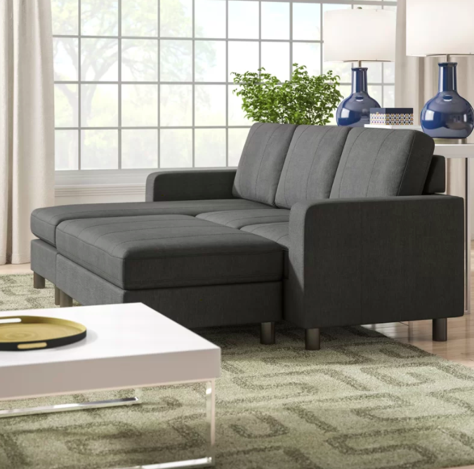 Gray reversible modular sofa and chaise set next to a white coffee table in a living room