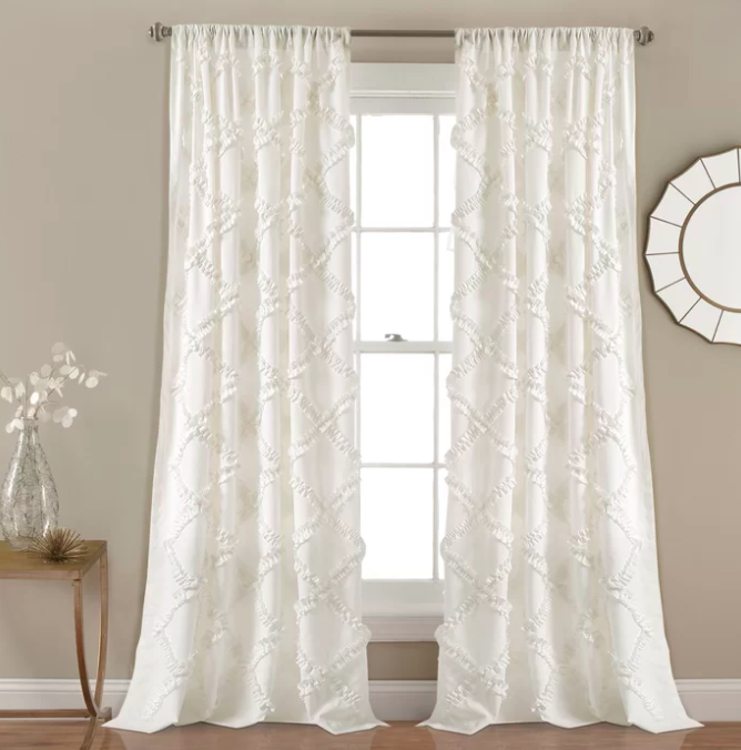 A pair of white semi-sheer thermal curtains against a large windowframe