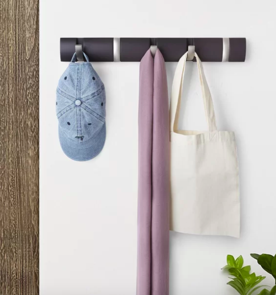 Espresso-colored wall hook with a denim hat, a pink scarf, and a white tote hanging from it