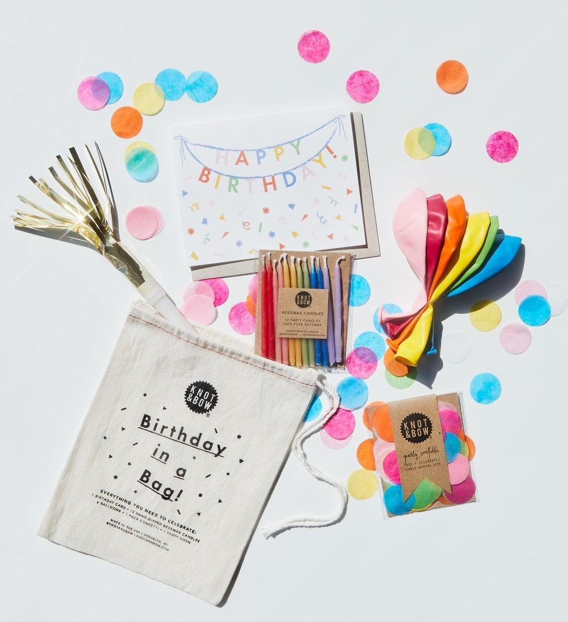 The various items that come with the birthday in a bag including the candles, balloons, card, confetti, and the bag