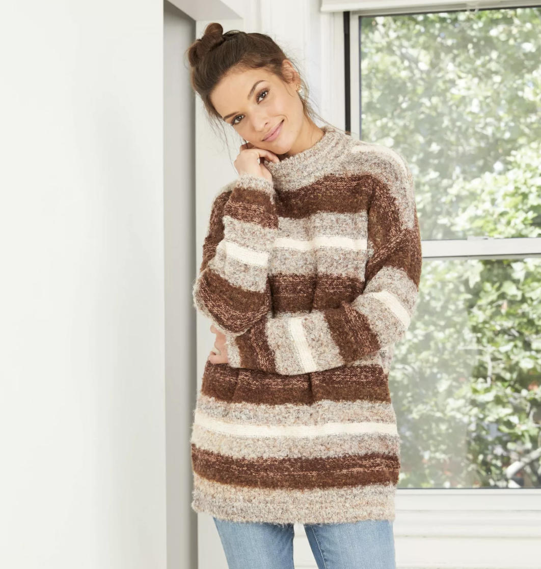 a model in a fuzyy sweater with tan, brown, and white vertical stripes